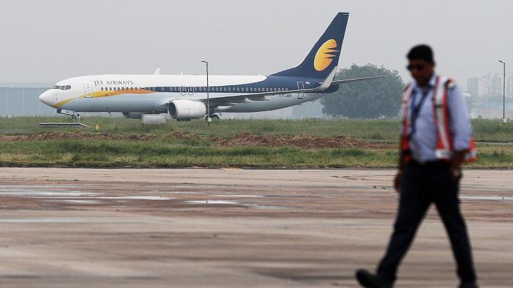 A Jet Airways Boeing 737 passenger plane moves on the runway as a man walks past at an airport in New Delhi