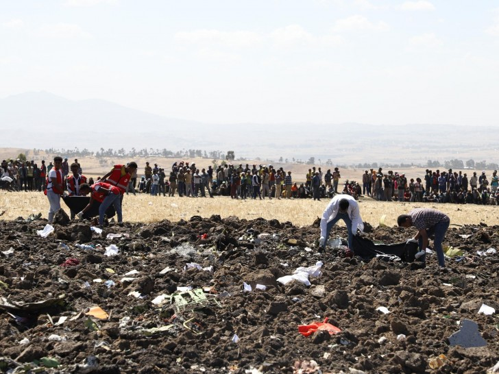 A rescue team collect remains of bodies amid debris at the crash site of Ethiopian Airlines Flight 302 near Bishoftu, a town some 37 miles southeast of Addis Ababa, Ethiopia, on Sunday.