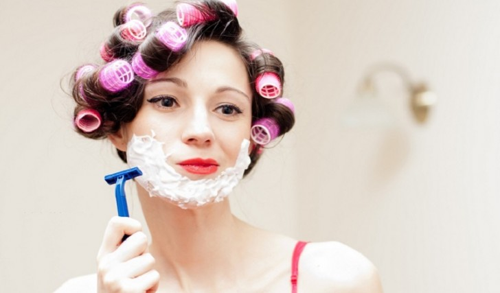 Beautiful funny young woman shaving with foam & razor her face