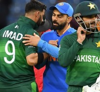 India's captain Virat Kohli (C) embraces Pakistan's Imad Wasim (L) after victory in the 2019 Cricket World Cup group stage match between India and Pakistan at Old Trafford in Manchester, northwest England, on June 16, 2019. (Photo by Dibyangshu SARKAR / AFP) / RESTRICTED TO EDITORIAL USE